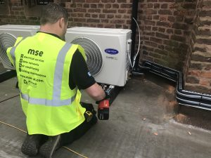 Man maintaining air conditioning unit