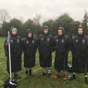 Rugby players wearing sponsor coats